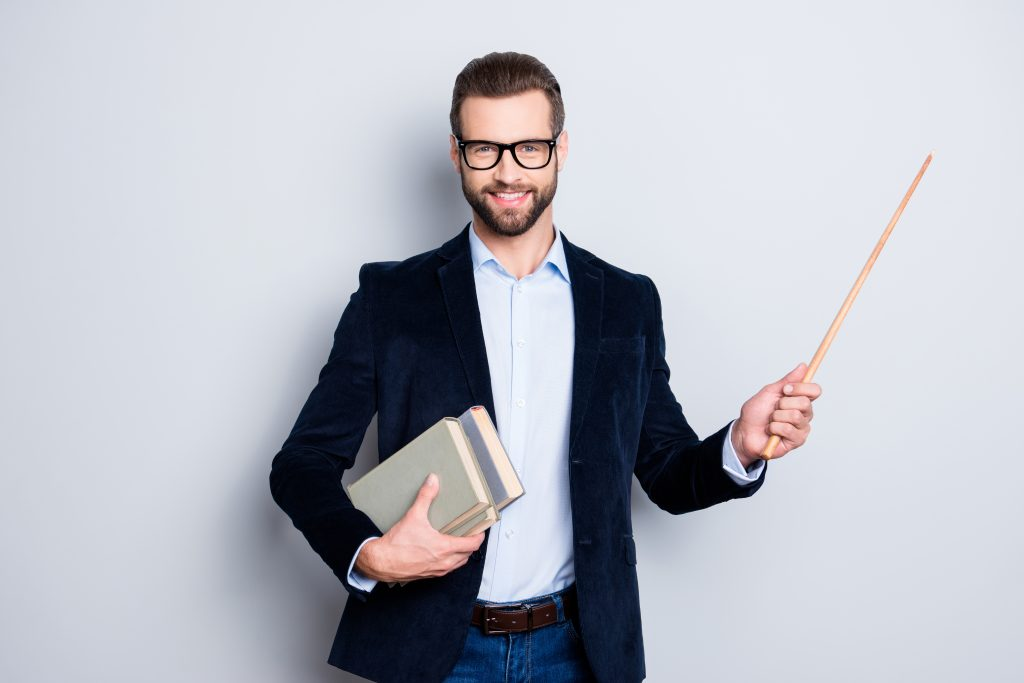 Portrait of cheerful teacher with stubble in shirt jacket, having books in hand and showing with pointer on empty place, copy space, looking at camera, isolated on grey background