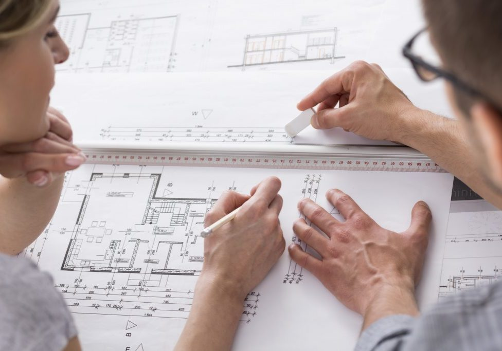 View of two focused architects working on some professional drawing